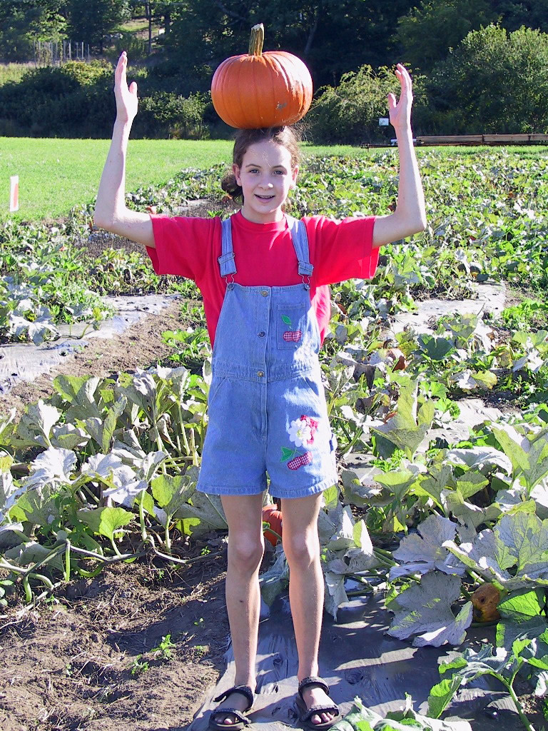 Girl balancing a pumpkin on her head
